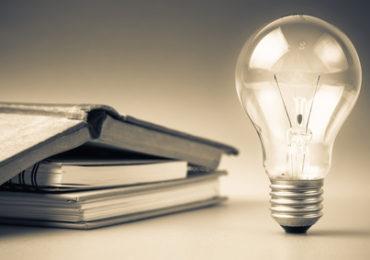 Light bulbs glowing with book